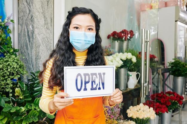 Jovem dona de floricultura usando máscara médica na entrada com placa aberta