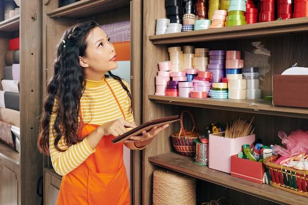 Jovem dono de floricultura asiática com tablet digital parado na prateleira cheia de fitas e pedindo mais produtos artesanais para decoração de buquês na loja online