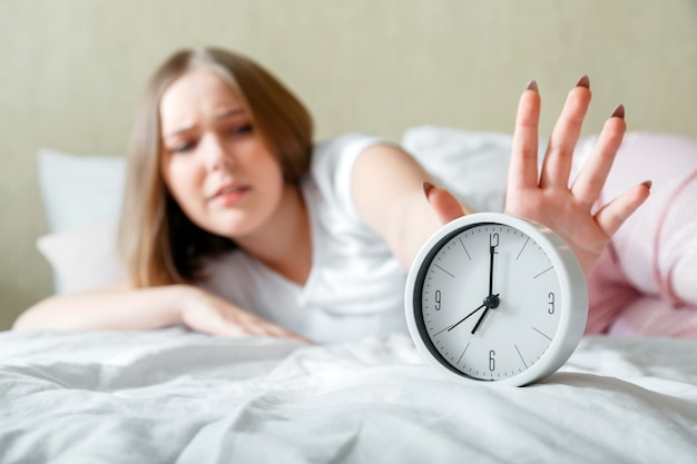 Jovem dormente acordada de pijama desliga o despertador com pressa. rotina matinal e acordar tarde do despertador na cama. mulher está atrasada em pânico após insônia e insônia. sono insalubre.
