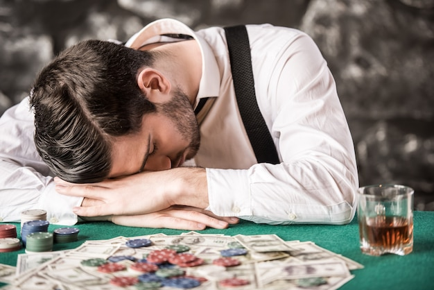 Jovem dormindo na mesa, enquanto está jogando o jogo de poker.