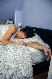 Jovem dormindo profundamente na cama em casa
