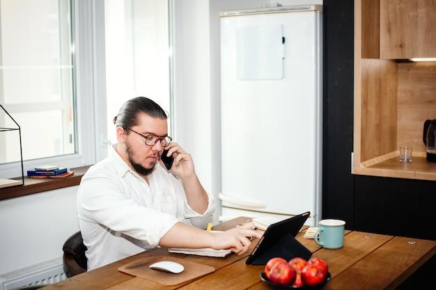 Jovem, durante o auto-isolamento, trabalha na cozinha de casa