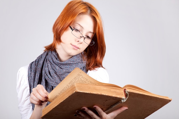 Jovem duvidando da moda de óculos com um livro velho
