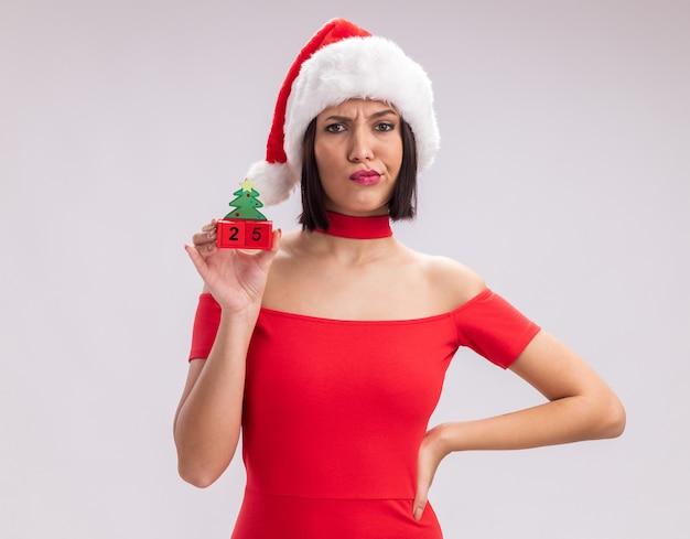 Jovem duvidosa com chapéu de papai noel segurando o brinquedo da árvore de natal com a data mantendo a mão na cintura, olhando para a câmera, isolada no fundo branco