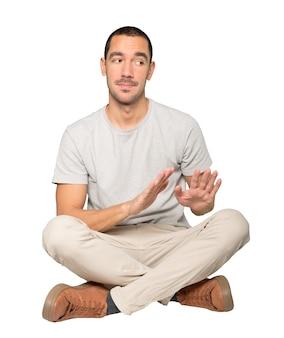 Jovem duvidoso fazendo um gesto de manter a calma