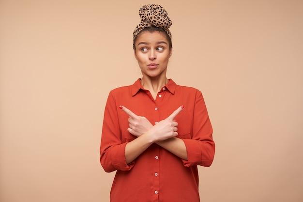 Jovem e adorável senhora de cabelos castanhos confusa, com maquiagem natural cruzando as mãos com os indicadores levantados enquanto olha de lado surpreso, posando sobre uma parede bege