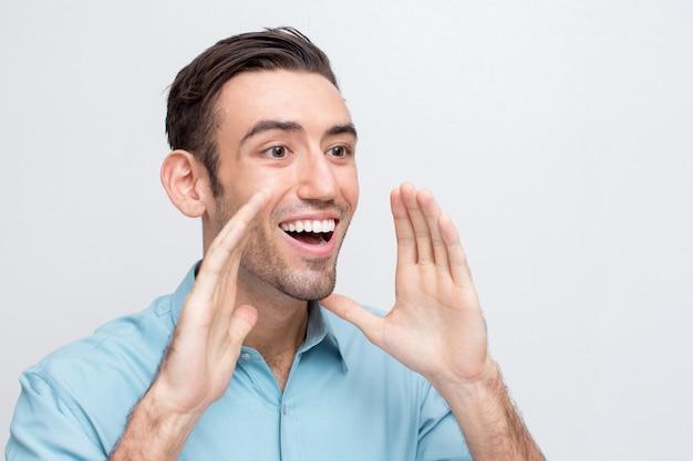 Jovem e alegre homem bonito indo gritar alto