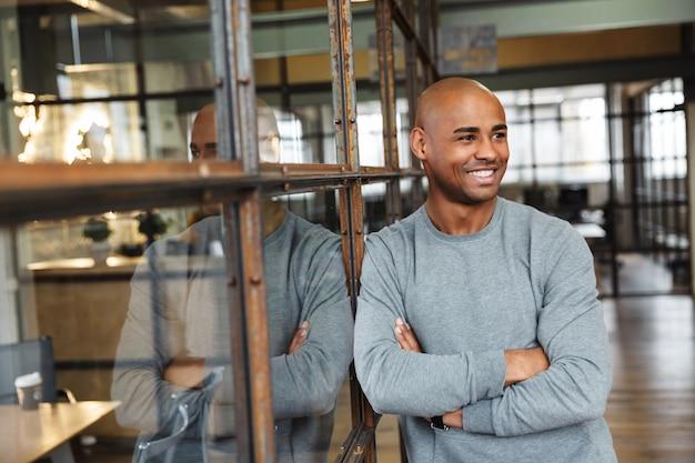 Jovem e atraente afro-americano careca em pé com os braços cruzados enquanto trabalhava no escritório