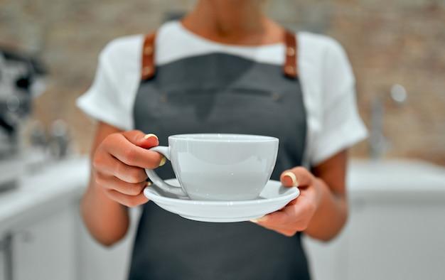Jovem e atraente barista está de pé no balcão de uma cafeteria e sorri, servindo uma xícara de café preparado para um cliente.