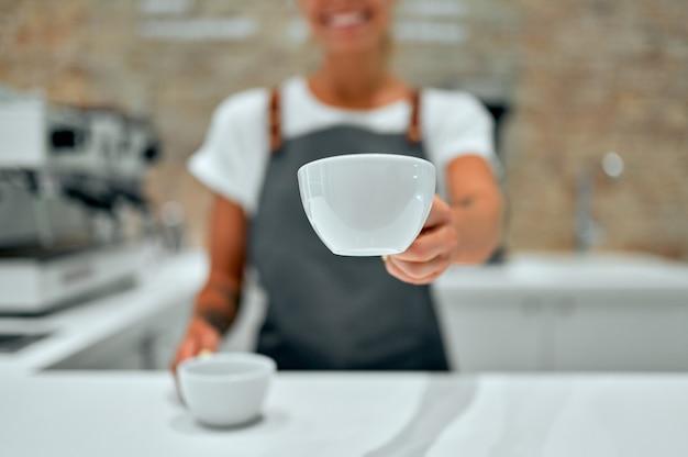 Jovem e atraente barista está de pé no balcão de uma cafeteria e sorri, servindo xícaras de café preparado para um cliente.