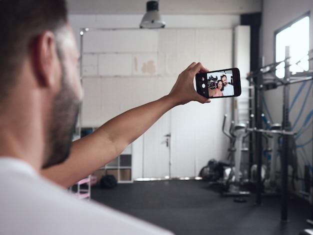 Jovem e atraente casal homem e mulher, sorrindo e posando ao fazer foto de selfie após a sessão de treino no ginásio. vista traseira, o casal é visto apenas na tela do celular, segura pela menina