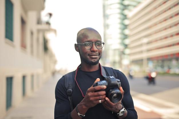 Jovem e atraente fotógrafo africano do sexo masculino com uma câmera em uma rua sob o sol