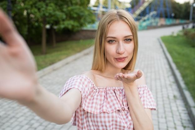 Jovem e atraente garota caucasiana tirando uma selfie em um smartphone e mostrando um beijo