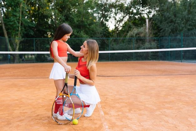 Jovem e atraente mãe ajuda a filha a jogar tênis