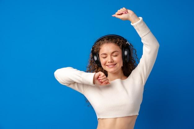 Jovem e atraente mulher encaracolada ouvindo música com fones de ouvido contra um fundo azul