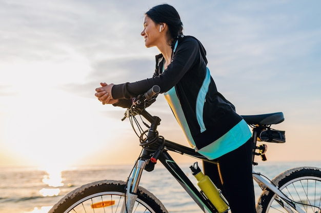 Jovem e atraente mulher magra andando de bicicleta, esporte na praia de verão ao nascer do sol da manhã em roupas de ginástica esportiva, estilo de vida saudável e ativo, sorrindo, feliz se divertindo