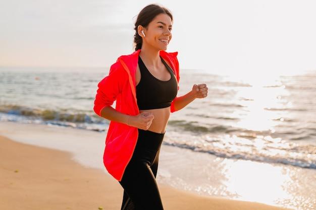 Jovem e atraente mulher magra fazendo exercícios ao nascer do sol da manhã, correndo na praia do mar com roupas esportivas, estilo de vida saudável, ouvindo música nos fones de ouvido e vestindo jaqueta corta-vento rosa