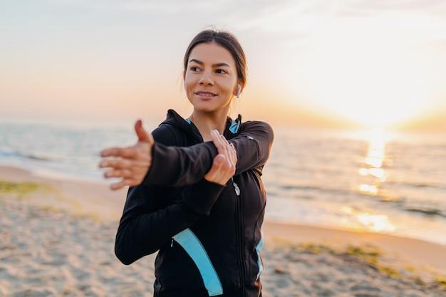 Jovem e atraente mulher magra fazendo exercícios de esporte na praia ao nascer do sol de manhã em roupas esportivas, estilo de vida saudável, ouvindo música em fones de ouvido, fazendo alongamento para as mãos