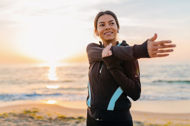 Jovem e atraente mulher magra fazendo exercícios esportivos na praia ao nascer do sol de manhã em roupas esportivas, estilo de vida saudável, ouvindo música em fones de ouvido, fazendo alongamento para os braços