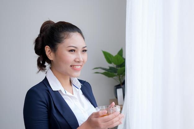 Jovem e atraente trabalhador de escritório bebendo chá, fazendo uma pausa para o café da manhã, preparando-se para o dia de trabalho