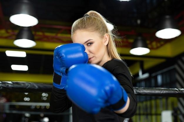 Jovem e bela atleta em poses de luvas de boxe azuis no ringue