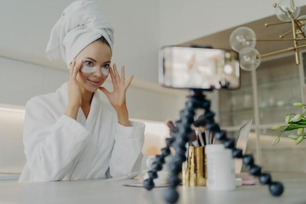 Jovem e bela blogueira de roupão de banho gravando um vídeo tutorial para blog de beleza ou mídia social sobre como usar adesivos cosméticos ou almofadas de olheiras enquanto está sentado na cozinha. conceito de cuidados com a pele
