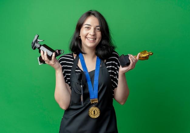 Jovem e bela cabeleireira com avental com medalha de ouro em volta do pescoço segurando troféu e spray feliz e animada em pé sobre a parede verde