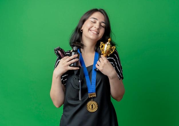 Jovem e bela cabeleireira com avental com medalha de ouro no pescoço segurando troféu e spray com aparador sorrindo com os olhos fechados em pé sobre a parede verde