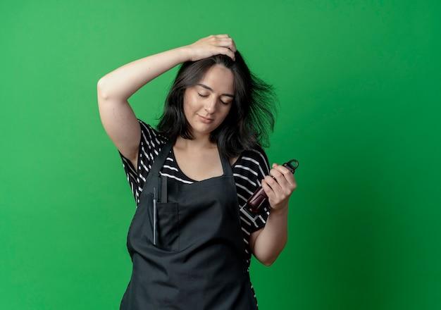 Jovem e bela cabeleireira com avental massageando o couro cabeludo em pé sobre a parede verde