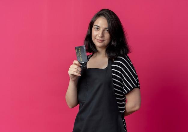 Jovem e bela cabeleireira com avental mostrando lookign de cartão de crédito para a câmera sorrindo rosa