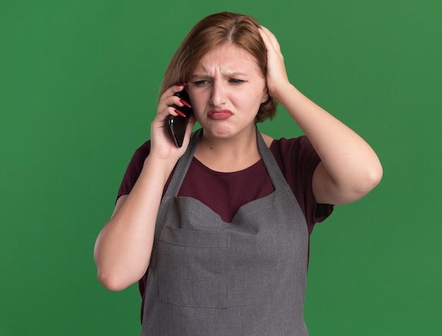 Jovem e bela cabeleireira com avental parecendo confusa enquanto fala no celular, em pé sobre a parede verde