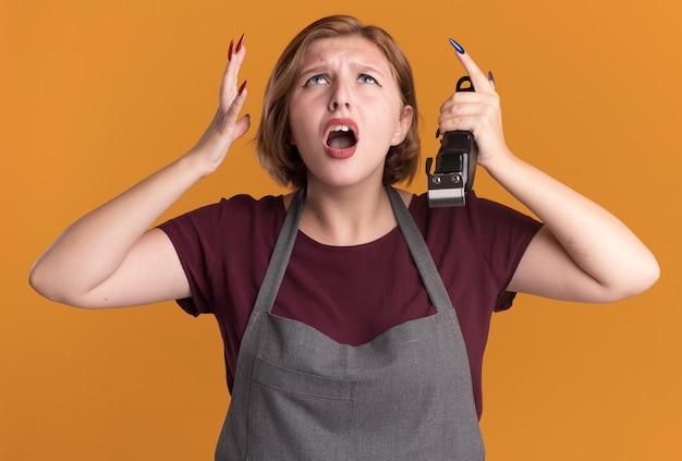 Jovem e bela cabeleireira com avental segurando o aparador, olhando para cima aborrecida e irritada, levantando os braços em pé sobre a parede laranja