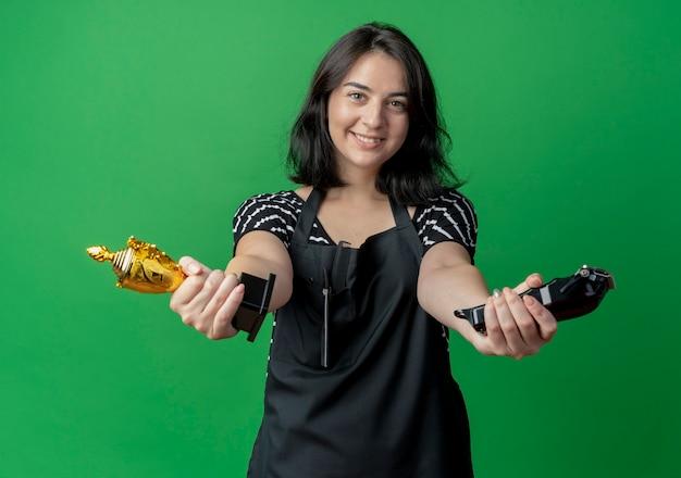 Jovem e bela cabeleireira com avental segurando troféu e aparador fazendo gesto de boas-vindas com as mãos bem abertas sobre o verde