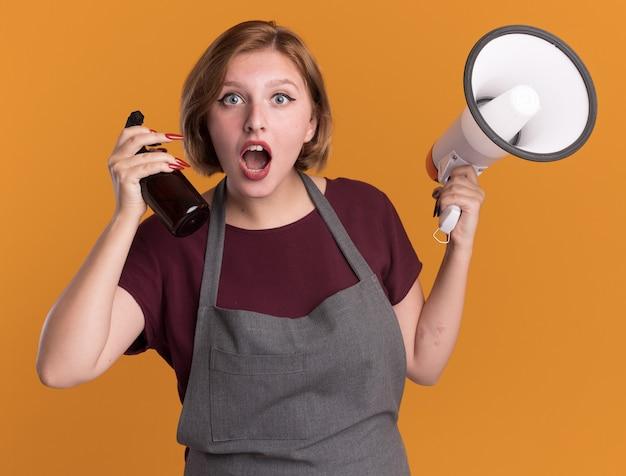 Jovem e bela cabeleireira com avental segurando um megafone e um frasco de spray louca olhando para a frente surpresa em pé sobre a parede laranja