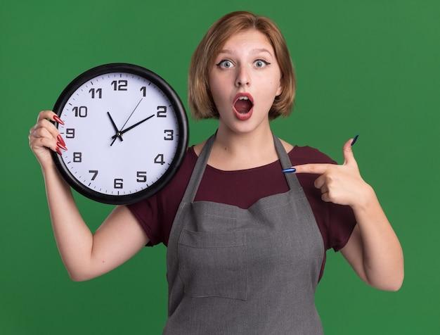 Jovem e bela cabeleireira com avental segurando um relógio de parede apontando com o dedo indicador para ele espantada e surpresa em pé sobre a parede verde