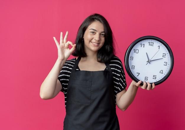 Jovem e bela cabeleireira com avental segurando um relógio de parede e mostrando um sinal de ok com um sorriso no rosto erguido sobre a parede rosa