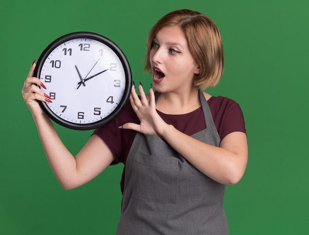 Jovem e bela cabeleireira com avental segurando um relógio de parede olhando para ela espantada e surpresa em pé sobre a parede verde