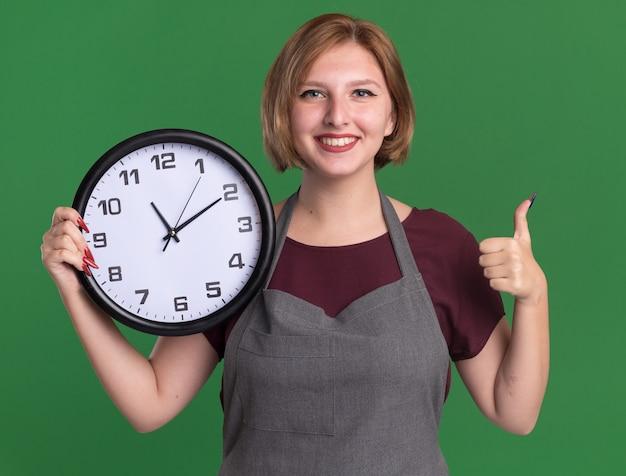 Jovem e bela cabeleireira com avental segurando um relógio de parede olhando para frente sorrindo alegremente mostrando os polegares para cima em pé sobre a parede verde