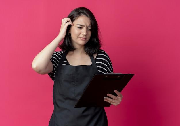 Jovem e bela cabeleireira com avental segurando uma prancheta e olhando para ela confusa sobre o rosa