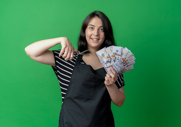 Jovem e bela cabeleireira com avental segurando uma tesoura e mostrando dinheiro sorrindo alegremente sobre o verde