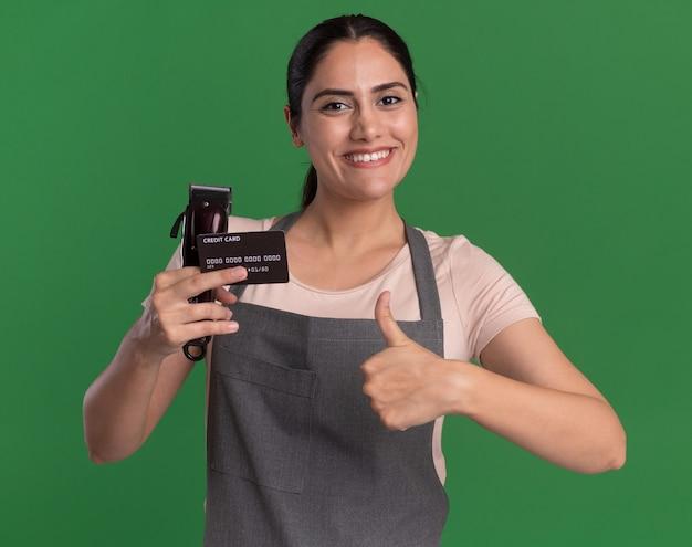 Jovem e bela cabeleireira de avental segurando o aparador e o cartão de crédito, olhando para frente com um sorriso no rosto mostrando os polegares em pé sobre a parede verde