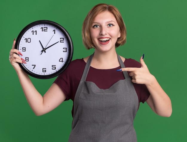 Jovem e bela cabeleireira de avental segurando um relógio de parede apontando com o dedo indicador para ele e sorrindo com uma cara feliz em pé sobre a parede verde