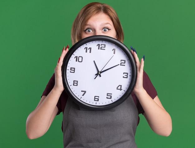 Jovem e bela cabeleireira de avental segurando um relógio de parede na frente do rosto, espiando por cima da parede verde