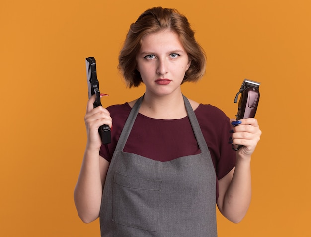 Jovem e bela cabeleireira de avental segurando uma máquina de cortar e uma arma olhando para frente com uma cara séria em pé sobre uma parede laranja