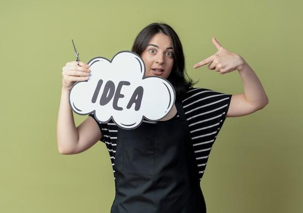 Jovem e bela cabeleireira de avental segurando uma tesoura e um balão de fala em branco com a palavra ideia apontando com o dedo para ela sorrindo em pé sobre a parede de luz
