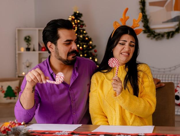Jovem e bela casal homem e mulher com bastões de doces se divertindo juntos, felizes e apaixonados em um quarto decorado de natal com árvore de natal na parede