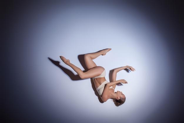 Jovem e bela dançarina em trajes de banho bege dançando no fundo do chão lilás