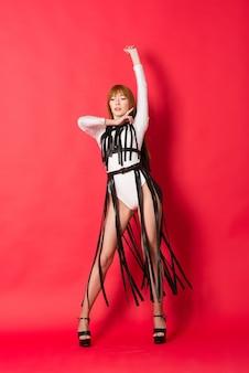 Jovem e bela dançarina posando em estúdio em fundo vermelho
