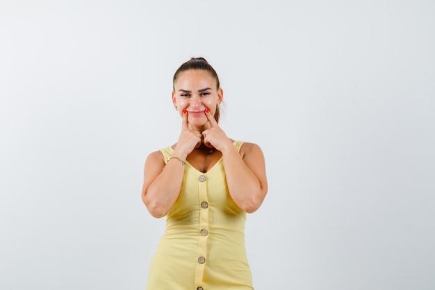 Jovem e bela fêmea pressionando os dedos nas bochechas no vestido e olhando alegre, vista frontal.