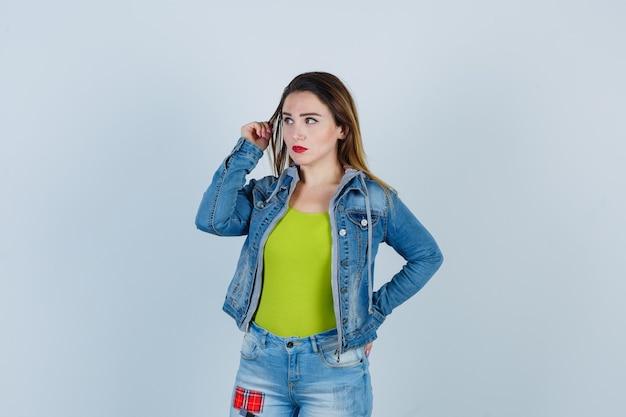 Jovem e bela fêmea segurando o cabelo enquanto olha de lado em roupa jeans e parece mal-humorada. vista frontal.